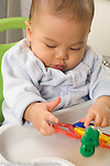 6 month old baby boy sitting in infant seat interested in toy using finger to spin plastic ball