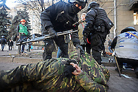 Policemen arrest some protesters in Maidan square while a medic helps a wounded demonstrator.  Kiev, Ukraine