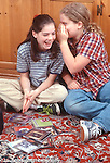 two 10 year old girls, friends, at home one whispering secret into the other's ear vertical