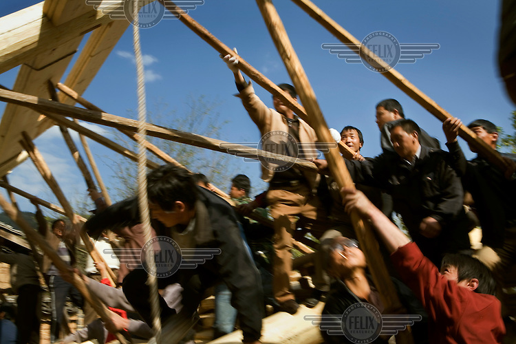 A traditional Nakhi (Naxi) ceremony for the erection of a new house. Usually most of the men from the community lend a hand in helping build a house, whilst the women cook.