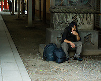 A homeless man in front of a temple entrance. He is not begging. He is just sitting there studying temple visitors and smoking his cigarettes.