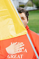 """A person holds a Gadsden flag and wears a """"Keep America Great"""" sweatshirt as people gather for an anti-lockdown protest organized by the alt-right group Super Happy Fun America near the home of Massachusetts governor Charlie Baker in Swampscott, Massachusetts, on Sat., May 16, 2020. The protest was in defiance of Massachusetts orders mandating face coverings and social distancing and prohibiting gatherings larger than 10 people during the ongoing Coronavirus (COVID-19) global pandemic. The state's stay-at-home order is expected to be updated on May 18, 2020, with a phased reopening plan issued by the governor as COVID-19 cases continue to decrease. Anti-lockdown protests such as this have become a conservative cause and have been celebrated by US president Donald Trump. Many of the protestors displayed pro-Trump messages or wore Trump campaign hats and shirts with phrases including """"Trump 2020"""" and """"Keep America Great."""" Super Happy Fun America, organizers of the protest, are an alt-right organization best known for creating the 2019 Boston Straight Pride Parade."""