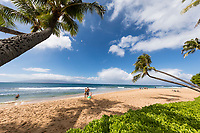A family enjoys a day under the palm trees at Ka'anapali Beach, Maui. (NOTE:  The family is model released, but not surrounding people.)