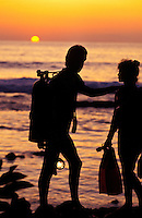 A couple holding scuba gear is silhouetted against a golden sunset at Kona on the Big Island of Hawaii.