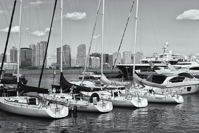 Sailboats, yachts, and pleasure boats are docked in the North Cove Marina in New York City with buildings of Jersey City, New Jersey visible across the Hudson River.  The North Cove Marina is located in Battery Park City in lower Manhattan.
