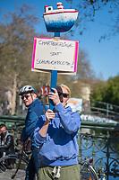 """Mit Transparenten, Plakaten und Flyern protestierten am Sonntag den 19. April 2020 in Berlin Menschen mit mehreren Flashmobs """"gegen das europaeische Grenzregime und die immer weiter zunehmenden Verbote der Meinungsaeusserung"""". Sie hielten dabei Schilder und Transparente, auf denen sie z.B. die Aufnahme der Fluechtlinge in den griechischen Fluechtlingslagern wie Moria forderten oder den Kapitalismus als Ursache fuer die Corona-Krise nannten.<br /> Im Bild: Menschen beim Flashmob auf der Admiralbruecke in Berlin Kreuzberg.<br /> 19.4.2020, Berlin<br /> Copyright: Christian-Ditsch.de<br /> [NUR FUER REDAKTIONELLE ZWECKE! Werbung nur auf Anfrage beim Fotografen. Inhaltsveraendernde Manipulation des Fotos nur nach ausdruecklicher Genehmigung des Fotografen. Vereinbarungen ueber Abtretung von Persoenlichkeitsrechten/Model Release der abgebildeten Person/Personen liegen nicht vor. NO MODEL RELEASE! Don't publish without copyright Christian-Ditsch.de, Veroeffentlichung nur mit Fotografennennung, sowie gegen Honorar, MwSt. und Beleg. Konto: I N G - D i B a, IBAN DE58500105175400192269, BIC INGDDEFFXXX, Kontakt: post@christian-ditsch.de<br /> Bei der Bearbeitung der Dateiinformationen darf die Urheberkennzeichnung in den EXIF- und  IPTC-Daten nicht entfernt werden, diese sind in digitalen Medien nach §95c UrhG rechtlich geschuetzt. Der Urhebervermerk wird gemaess §13 UrhG verlangt.]"""