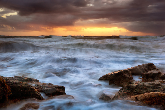A distant storm looms as the incoming tide approaches the rocky shoreline.