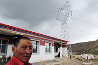 A Tibetan man stands outside of a new building on the Tibetan Plateau, in western China. Relocation communities been created to house nomadic herders moved from the highland grasslands. The nomads have been blamed for contributing to the deterioration of the grasslands, so have been moved, sometimes forcibly, into newly built towns that can be found across the plateau.