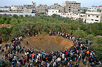 "Palestinians are gather arround a huge hall on the ground from an Israeli missile strke in afarm in Jabaliya refugee camp, nourthern Gaza Strip March,01,2008.""photo by Fady Adwan"""