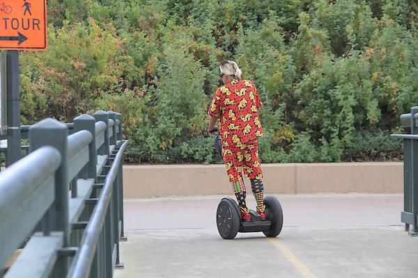 Man riding a Segway on a sidewalk in Denver, Colorado.