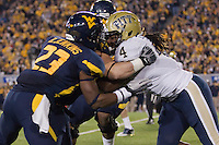 """WVU defensive back Brodrick Jenkins (23) and Pitt running back Zach Brown butt heads in the """"Backyard Brawl"""". The WVU Mountaineers beat the Pitt Panthers 21-20 at Mountaineer Field in Morgantown, West Virginia on November 25, 2011."""