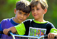 Closeup of two young boys on a bike.