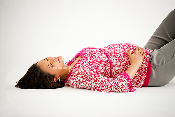 Pregnant Hispanic woman laying down with eyes closed, hands on stomach