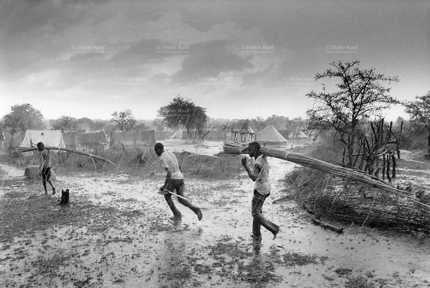 Uganda. West Nile. Adjumani. Ogujebe is distant 15 km from Adjumani. It is a transit camp for refugees from South Sudan. A group of men walk under the heavy rain storm. West Nile sub-region (previously known as West Nile Province and West Nile District) is a region in north-western Uganda. © 1989 Didier Ruef