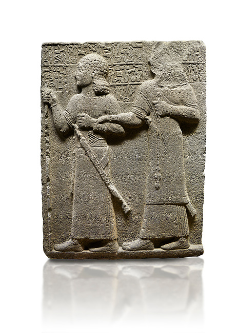 """Hittite monumental relief sculpted orthostat stone panel of Royal Buttress. Basalt, Karkamıs, (Kargamıs), Carchemish (Karkemish), 900-700 B.C. Anatolian Civilisations Museum, Ankara, Turkey.<br /> <br /> King Araras holds his son Kamanis from the wrist. King carries a sceptre in his hand and a sword at his waist while the prince leans on a stick and carries a sword on his shoulder. <br /> <br /> Hieroglyphs reads; """"This is Kamanis and his siblings. I held his hand and despite the fact that he is a child, I located him on the temple. This is Yariris' image"""".  <br /> <br /> Against a white background."""