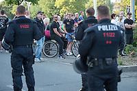 """Nach den pogromartigen Ausschreitungen gegen eine Fluechtlinsunterkunft im saechschen Heidenau am Freitag den 21. August 2015 durch Anwohnerinnen der Ortschaft, kamen am Samstag de 22. August 2015 ca. 250 Menschen in die Ortschaft um ihre Solidaritaet mit den Gefluechteten zu zeigen.<br /> Am Vorabend hatten Rassisten, Nazis und Hooligans sich zum Teil Strassenschlachten mit der Polizei geliefert um zu verhindern, dass Fluechtlinge in einen umgebauten Baumarkt einziehen. Ueber 30 Polizisten wurden dabei verletzt.<br /> Bis in die Abendstunden des 22. August blieb es trotz spuerbarer Anspannung um die Unterkunft ruhig. Im Laufe des Tages wurden immer wieder Gefluechtete mit Reisebussen gebracht was von den wartenenden Heidenauern mit Buh-Rufen begleitet wurde. Vereinzelt wurde auch """"Sieg Heil"""" gerufen, was die Polizei jedoch nicht verfolgte.<br /> Kurz vor 23 Uhr griffen Nazis und Hooligans wie am Vorabend die Polizei mit Steinen, Flaschen, Feuerwerkskoerpern und Baustellenmaterial an. Die Polizei mussten mehrfach den Rueckzug antreten, scheuchte den Mob dann von der Fluechtlingsunterkunft weg. Dabei wurden auch wieder Traenengasgranaten verschossen. Mindestens ein Nazi wurde festgenommen.<br /> Im Bild: Etliche Rassisten haben sich der antirassistischen Kundgebung genaehert und werden von der  Polizei aufgefordert sich zu enfernen. Ihnen wird ueber den Lautsprecher eines Polizeifahrzeuges angeboten auf der gegenueberliegenden Strassenseite eine Kundgebung anzumelden.<br /> 22.8.2015, Heidenau/Sachsen<br /> Copyright: Christian-Ditsch.de<br /> [Inhaltsveraendernde Manipulation des Fotos nur nach ausdruecklicher Genehmigung des Fotografen. Vereinbarungen ueber Abtretung von Persoenlichkeitsrechten/Model Release der abgebildeten Person/Personen liegen nicht vor. NO MODEL RELEASE! Nur fuer Redaktionelle Zwecke. Don't publish without copyright Christian-Ditsch.de, Veroeffentlichung nur mit Fotografennennung, sowie gegen Honorar, MwSt. und Beleg. Konto: I N G - D i B a, I"""