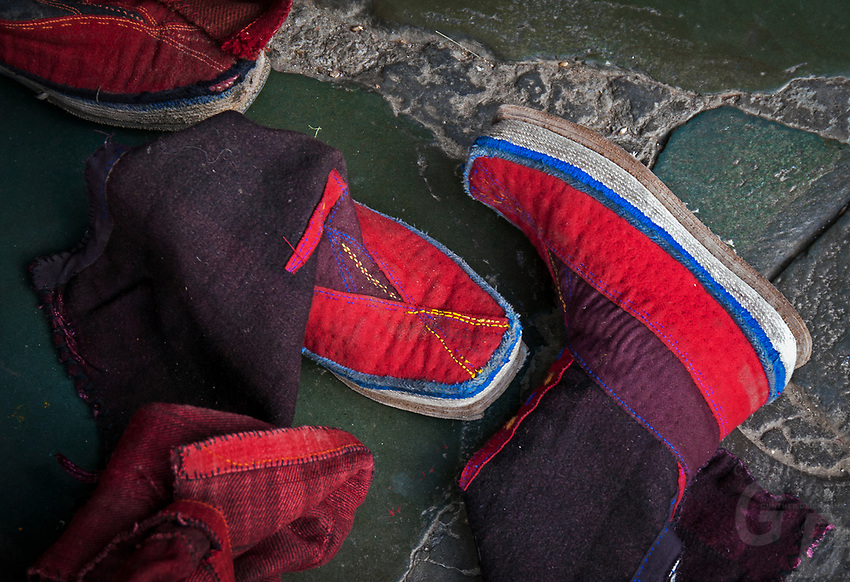 Buddhist Monks Boots outside the entrance of the Prayer hall. Tibet, China