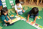 Education preschool 3-4 year olds two boys and a girl working together on floor puzzle using illustration on box to guide them