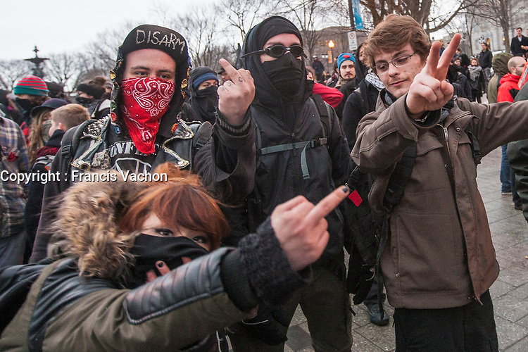 """A protester makes the """"peace sign"""" as other masked protesters show the middle finger during a protest against austerity organized by the ASSE student group in Quebec city Thursday March 26, 2015.<br /> <br /> PHOTO :  Francis Vachon - Agence Quebec Presse"""