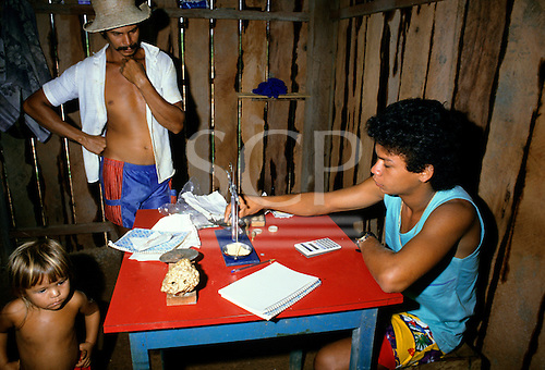 Ouro Verde, Xingu, Brazil. Garimpo illegal gold mine; weighing the gold on a balance in a rough timber shack.