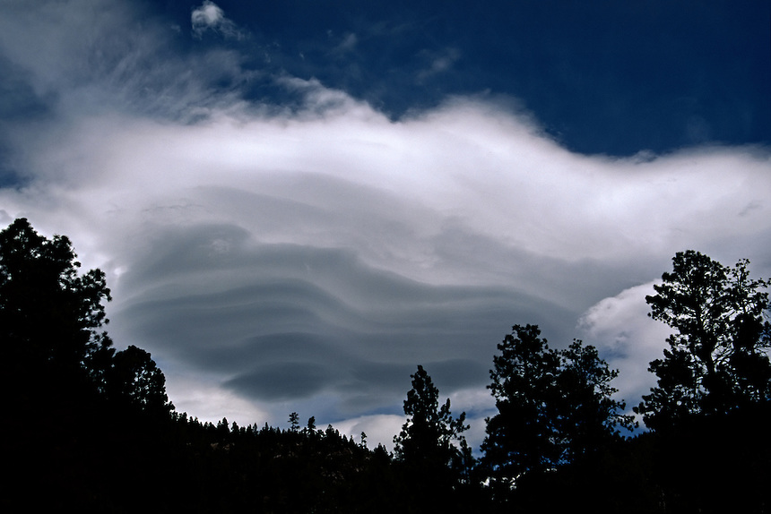 The tiered structure of a mountain lenticular wave cloud develops near Flagstaff Arizona in August. Lenticular clouds are stationary oblong or lens-shaped clouds which form at high altitudes usually at right angles to the wind direction when moist air flows over mountains.