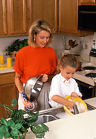 A smiling mother and young daughter washing dishes in the kitchen.