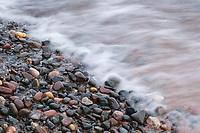 A wave off Lake Superior rushes in over tumbled beach rocks, Wisconsin.