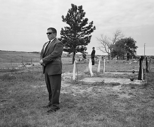 Wounded Knee, South Dakota<br /> July 28, 2011<br /> <br /> Secret Service men stand guard by graves at Wounded Knee on the Pine Ridge Reservation in South .Dakota during a brief visit by the United States Attorney General, Eric Holder. The mass grave at the .cemetery is where the victims of the 1896 massacre of Big Foot's band were buried. The U.S. Government has never formally apologized for the slaughter that took place there, when soldiers killed several hundred fleeing women in children, symbolically ending two centuries of war against this nation's original inhabitants