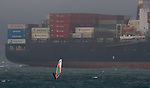 A windsurfer sailed past a super tanker on San Francisco Bay in San Francisco, California.