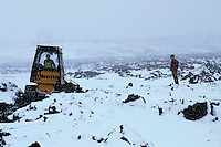 Two men busy constructing a road in heavy snowfall.
