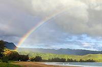 A rainbow brightens an overcast morning at Hanalei Beach and Hanalei Bay, Kaua'i.