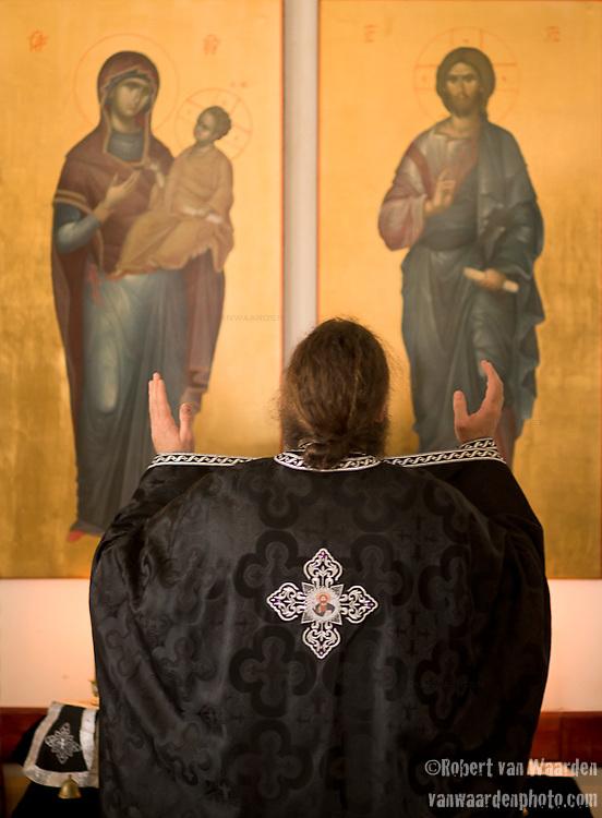 Father Iustin Petre prays during service.