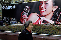 Woman passing advertising for Japanese Canon digital cameras in Shanghai, China..01 May 2005