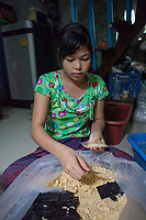 """Ma Thandar*, 15 years, packaging rice noodles. She is employed by Nila* and her husband who run a home-based business baking cakes and packaging dry noodles which are sold in local markets. """"We, the young girls working here, dropped school at the age of 10 and have been working in this business since we are 12. We do lighter work than the boys, for example packaging dry noodles in little plastic bags. We support our families in the village with this income"""", tells Ma Thandar*."""