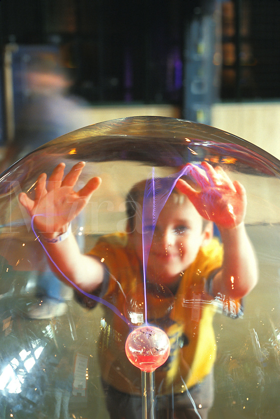 boy touching electric plasma ball Science Center Detroit Michigan