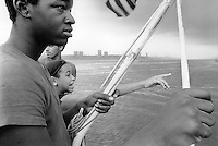 USA. New York City. Boat trip on the Hudson river for three friends. Richie, a young black Puerto Rican teenager from Spanish Harlem, a young boy pointing his finger and Carlos, who is Richie's cousin. 24.07.86 © 1986 Didier Ruef
