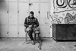 """GAZA, Beit Laya: Tarek, 19 years old, poses in his bedroom. On December 2018, he went to the Great March of return. Too close from the fence, he got shot in his left knee by an explosive bullet. After 10 days of trying to save his leg, the doctors of Al Shifa hospital decided that he should have an imputation to avoid a further infection. One year after the amputation, Tarek is looking for an articial leg but his bone keeps growing which makes it difficult to find the right prothesis...The 31th of October 2019.<br /> <br /> GAZA, Beit Laya: Tarek, 19 ans, joue sur son téléphone devant sa maison. En décembre 2018, il s'est rendu à la """"Grande Marche du Retour"""". Trop près de la clôture, il s'est fait tirer dans le genou gauche par une balle explosive. Après 10 jours à essayer de sauver sa jambe, les médecins de l'hôpital Al Shifa ont décidé qu'il devait subir une imputation pour éviter une nouvelle infection. Un an après l'amputation, Tarek cherche une jambe artificielle mais son os continue de grandir ce qui rend difficile la recherche de la bonne prothèse ... Le 31 octobre 2019."""