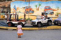 Tripoli, Libya, North Africa - Little Girl Watching Amusement Park Ride.