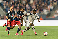 FOXBOROUGH, MA - JULY 25: Sunusi Ibrahim #22 of CF Montreal on the attack as Maciel #13 of New England Revolution defends during a game between CF Montreal and New England Revolution at Gillette Stadium on July 25, 2021 in Foxborough, Massachusetts.