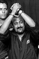 Marwan Barghouti, the West bank chief of Yasser Arafat's Fatah movement rice his handcuff hands in the courtroom on the opening day of his court case at Tel Aviv's District Court, August 14,2002. Israel charged Marwan Barghouti, the detained leader of Fatah's Tanzim militia in the West Bank and leader of the Palestinian uprising, with murder, incitement to murder, attempted murder, conspiracy, membership in a terrorist organization acting as accessory to murder, and activity in a terrorist organization. Photo by Quique Kierszenbaum