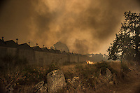 A wildfire rages along a cemetary wall in Lucenza, in Cualedro, near Ourense on August 30, 2015. A fire broke out on August 30, 2015 around noon in the Cualedro town in Galicia, northwest Spain, affecting at least 3,180 hectares of forest, as seven fires continued to burn in Spain, three in Galicia, one in Cantabria, one in Castile and Leon, one in Catalonia and Extremadura. © Pedro ARMESTRE