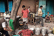 Street side vendors prepare food and carry on with their morning chores on the streets of Kolkata in West Bengal, India.
