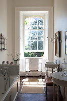 One of several bathrooms is flooded with sunlight from a window overlooking the garden