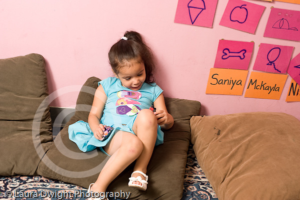 Education Preschool 4-5 year olds girl playing with small toy vehicle rolling it on her knee horizontal playing alone