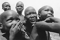 Uganda. West Nile. Adjumani. Ogujebe is distant 15 km from Adjumani and is a transit camp for refugees from South Sudan. A group of five young boys laughs and has fun.  West Nile sub-region (previously known as West Nile Province and West Nile District) is a region in north-western Uganda. © 1989 Didier Ruef