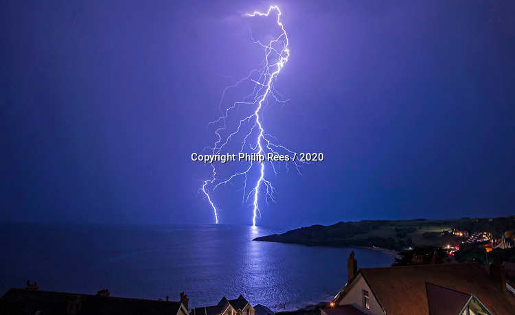 Langland Bay, Swansea, UK, 25th June 2020.<br />Beachgoers are treated to a spectacular light show by mother nature tonight at Langland Bay near Swansea as fork lightning discharges off Snapple Point, spelling an end to the recent UK heatwave.