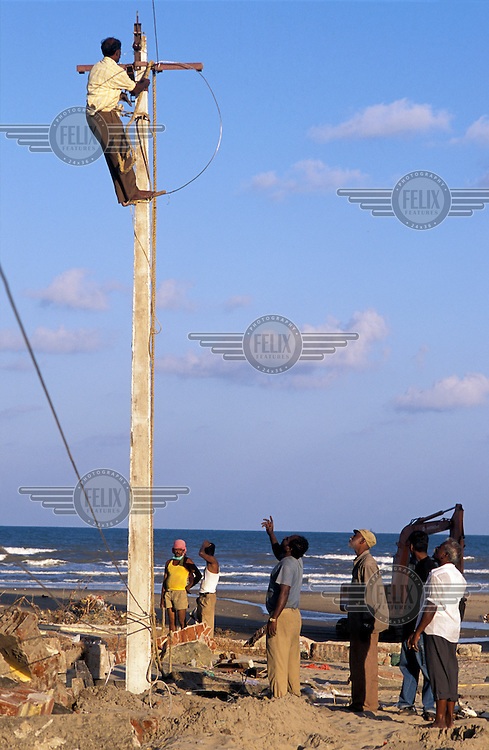 Electricity lines being repaired following the tsunami which struck South Asia on 26/12/2004..An underwater earthquake measuring 9 on the Richter scale triggered a series of tidal waves which caused devastation when they struck dry land. 12 countries were affected by the tsunami, with a combined death toll of over 150,000.