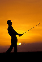 Silhouette of man playing golf at sunset