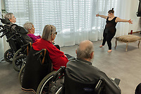 "Switzerland. Canton Ticino. Gordola. Casa Riposo (Retirement Home) Solarium. MOPS_DanceSyndrome is an independent Swiss artistic, cultural and social organisation operating in the field of contemporary dance and disability. It is composed only of Down dancers. Amedea Aloisi on stage during ""Choreus Numinis"" show. Down syndrome (DS or DNS), also known as trisomy 21, is a genetic disorder caused by the presence of all or part of a third copy of chromosome 21 It is usually associated with physical growth delays, mild to moderate intellectual disability, and characteristic facial features. A group of elderly people, all seated in wheelchairs, look at the woman dancing. A retirement home – sometimes called an old people's home or old age home - is a multi-residence housing facility intended for the elderly. Gordola is a municipality in the district of Locarno. 29.11.2019 © 2019 Didier Ruef"