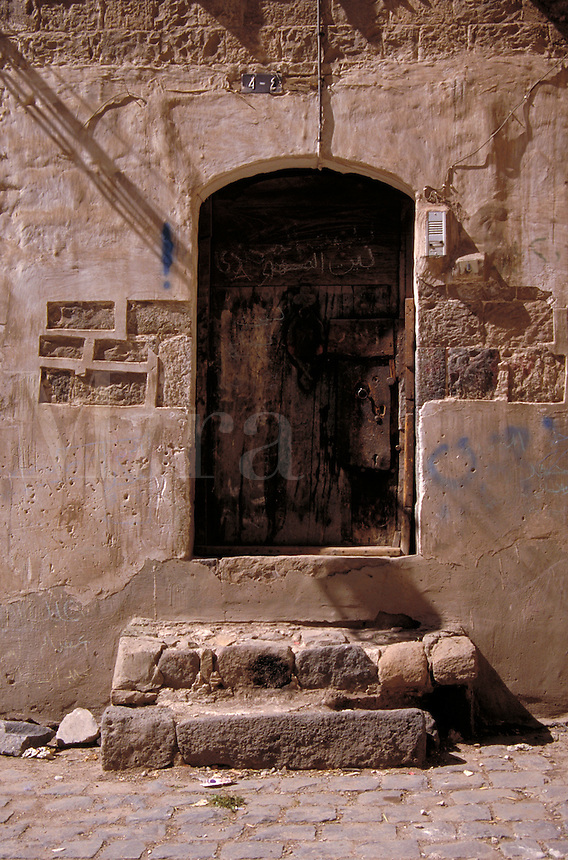 Steps leading up to an old wooden doorway inlaid in a mud brick wall. Architecture. Sana, Yemen.